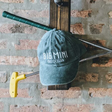 Green dad hat with white in-line logo in front of brick and wood