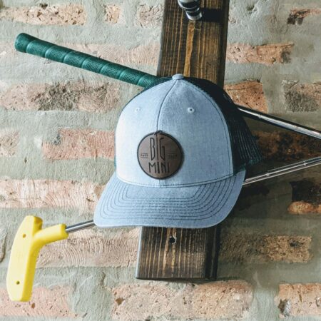 Green mesh back trucker hat with tan circle logo patch in front of brick and wood