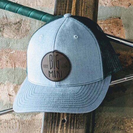 Green mesh back trucker hat with tan patch on top of crossed putters