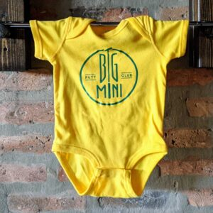 Yellow baby onesie with green circle logo